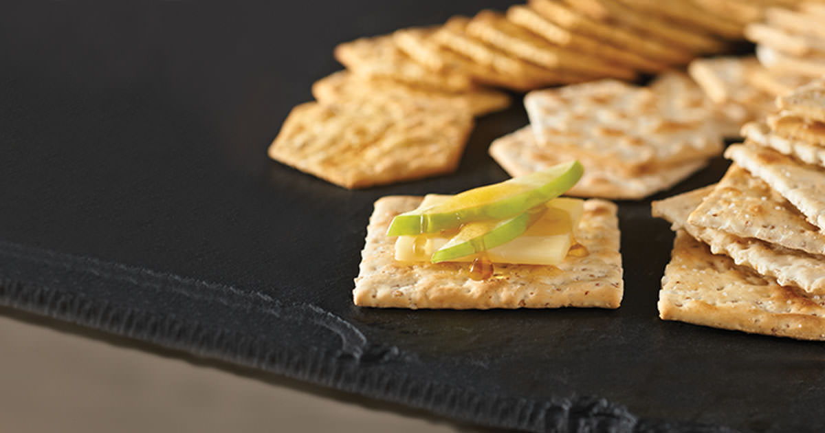Slices of Granny Smith apples and Vermont white cheddar on Mariner stoned wheat crackers, looking all delicious